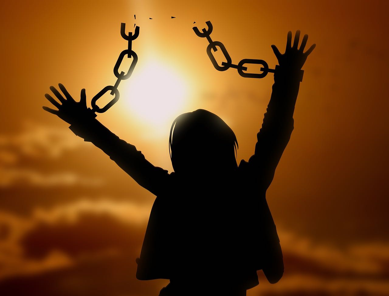 Person breaking free of chains attached to wrists with sunset in background