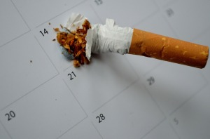 Cigarette being stubbed out on specific day of calendar