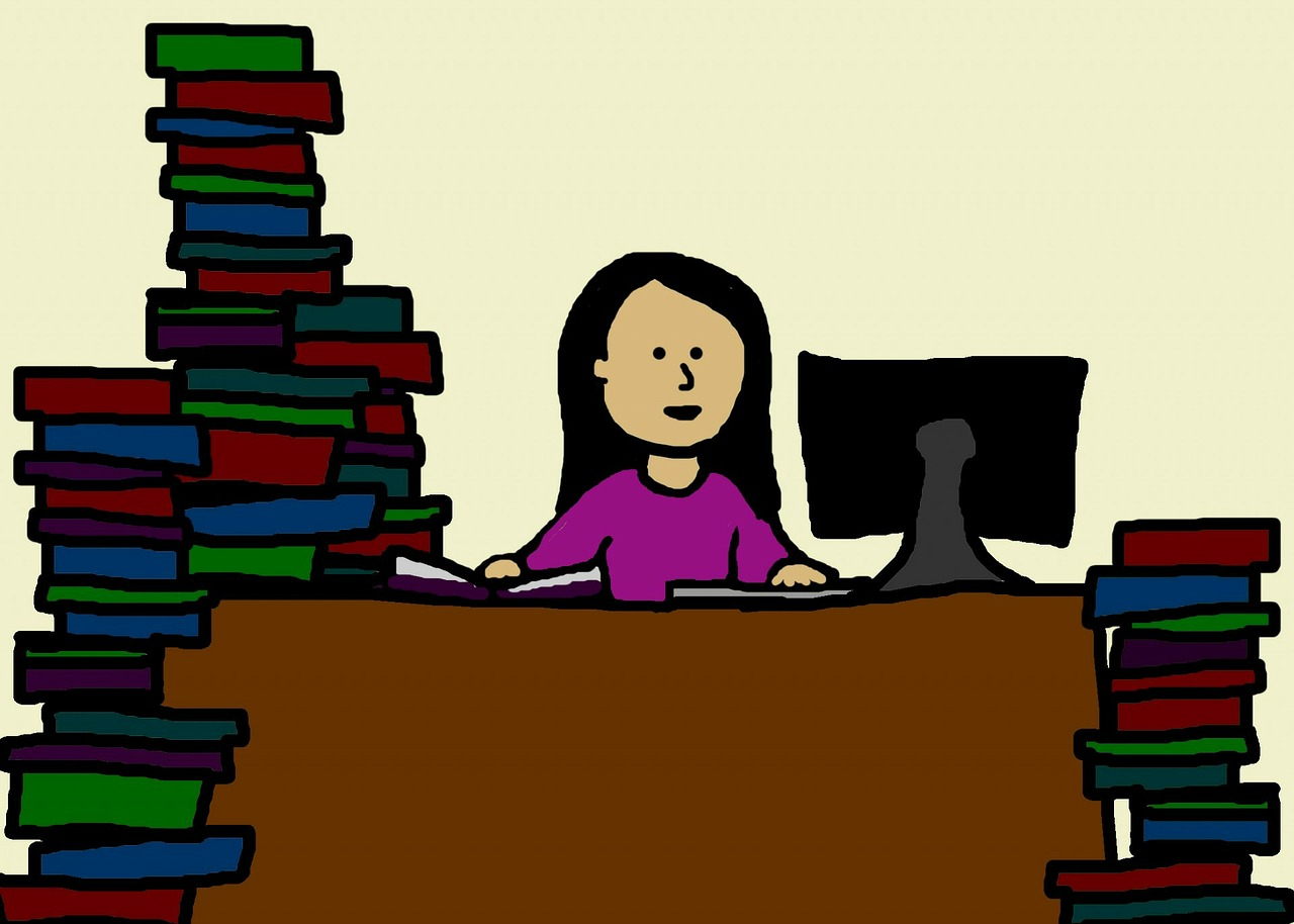 woman sitting at desk with large piles of books