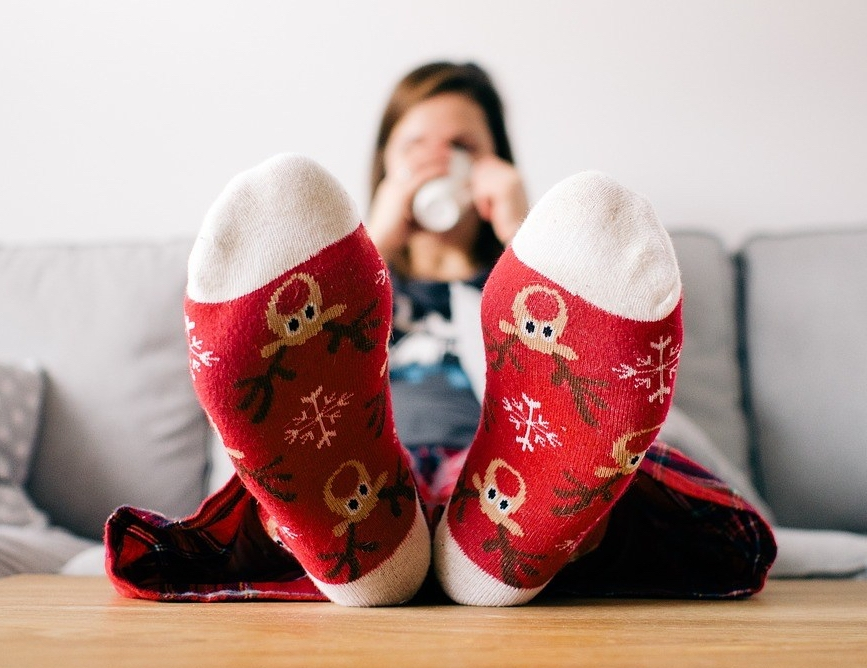 Picture of woman in pyjamas and wearing Christmas socks, drinking a hot drink