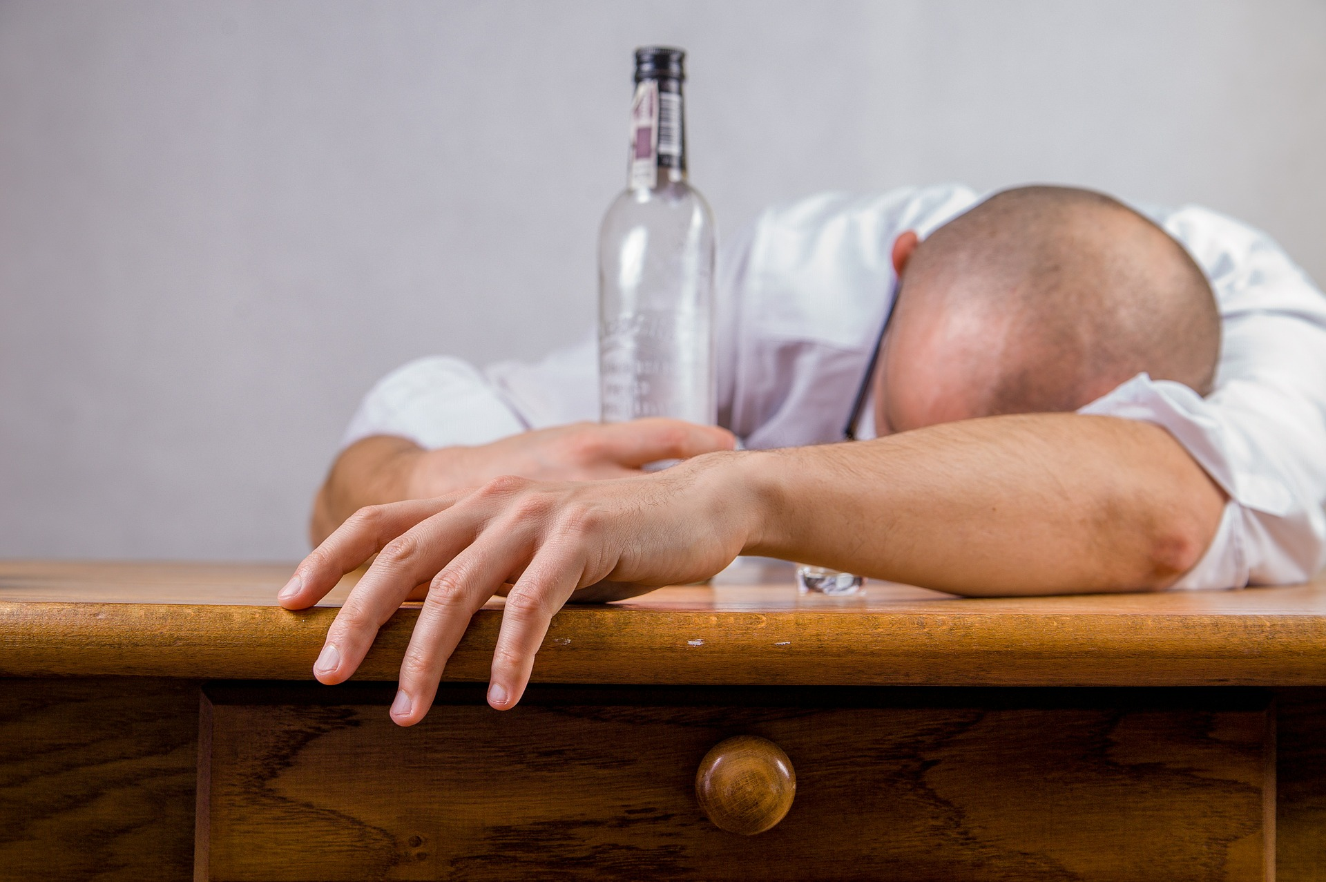 Man slumped over desk with empty alcohol bottle in his hand