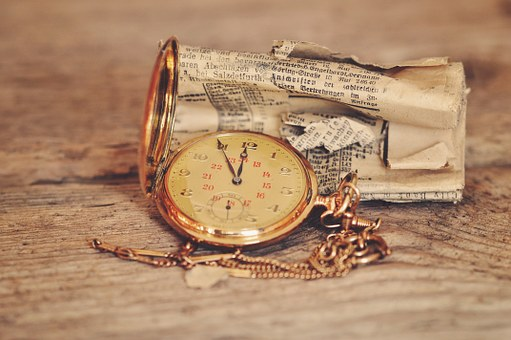 Pocket watch sitting on top of old newspaper