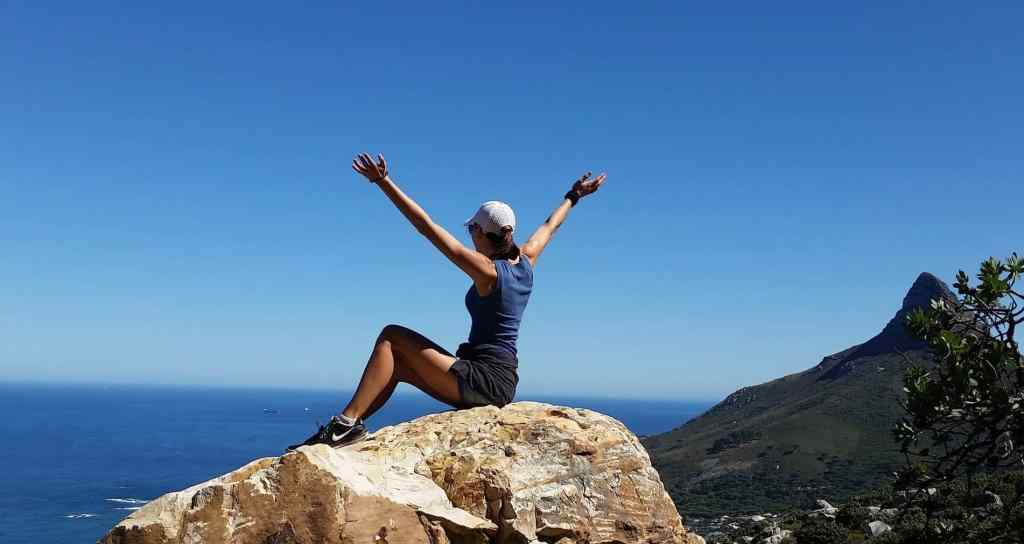 woman sitting on top of mountain with hands outstretched in air