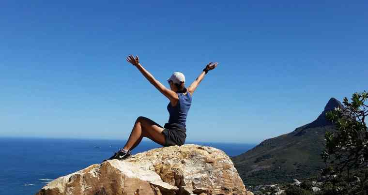 Girl sitting on top of mountain with arms outstretched