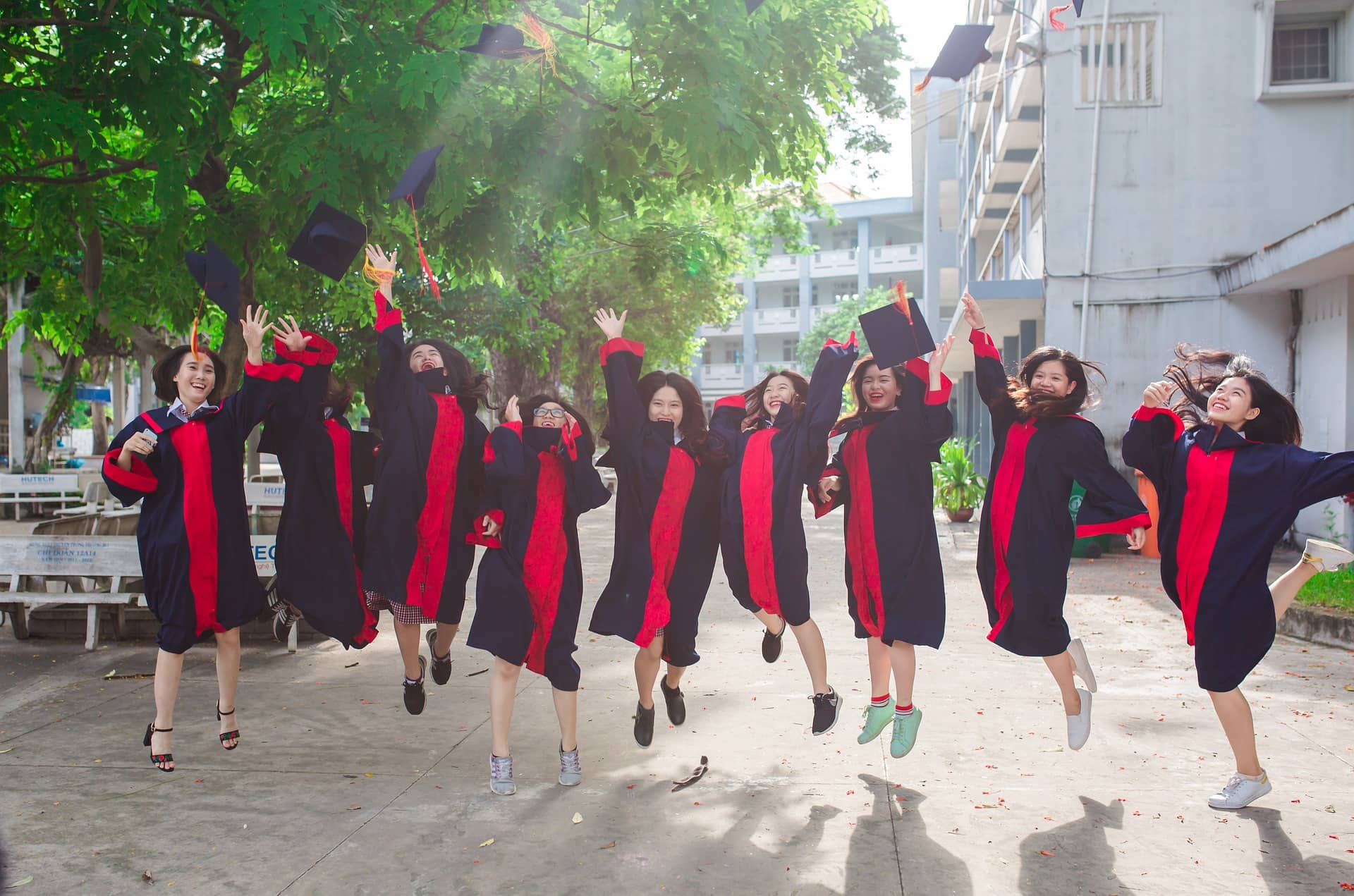 group of female graduates jumping for joy