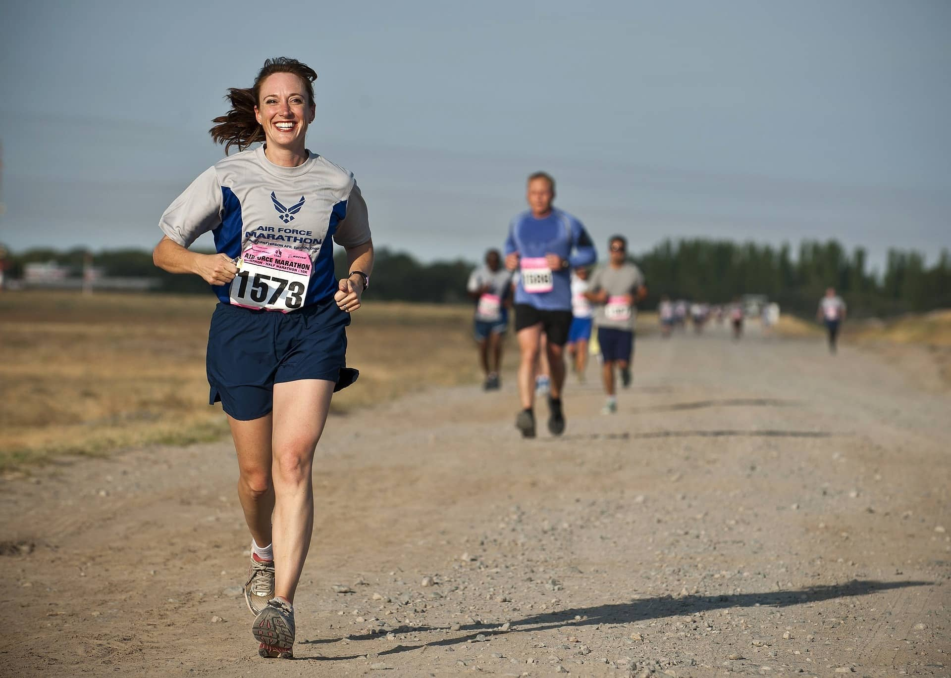 woman running down road, other runners in background