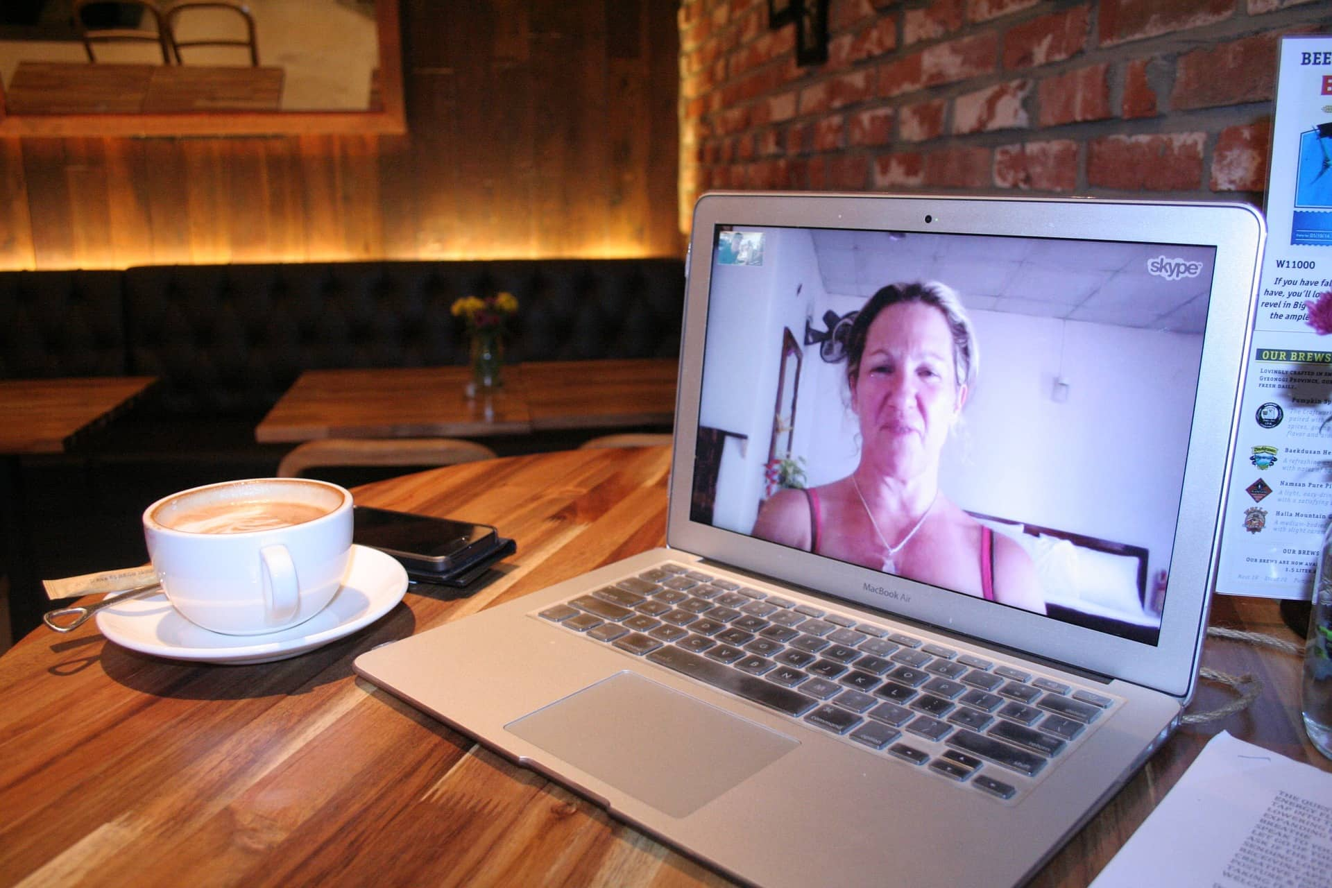 laptop and coffee cup on desk, picture of woman showing on laptop