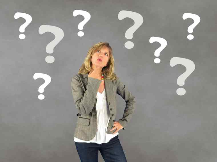 woman looking upwards with question marks in background
