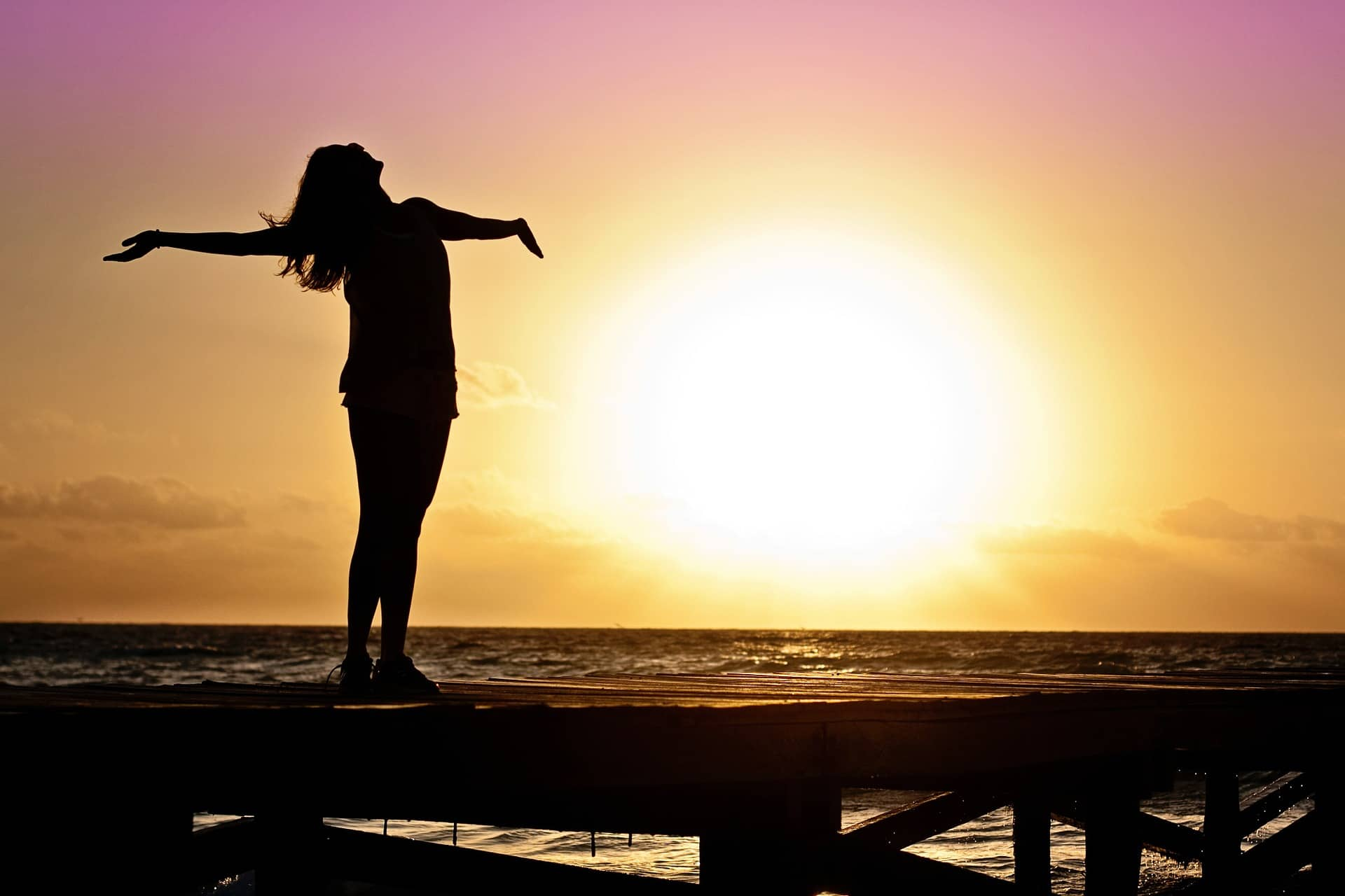 woman standing on jetty facing sun with arms outstretched