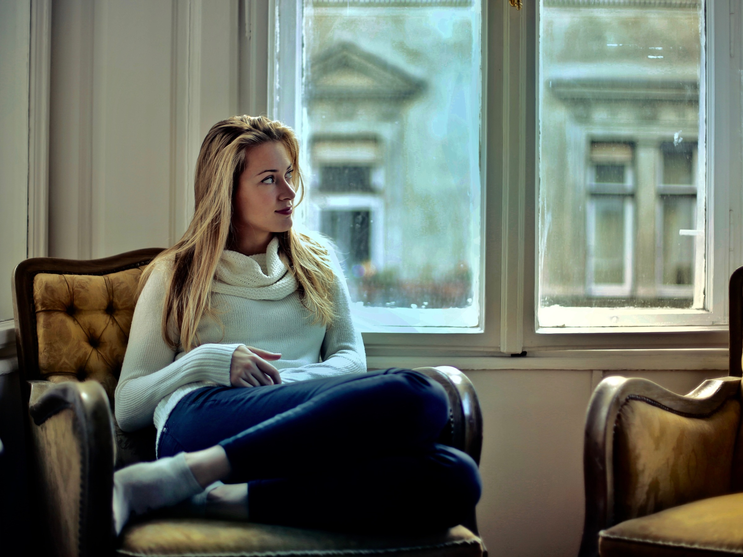 woman sitting on couch near window